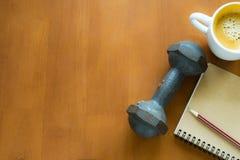 Dumbbel, kawa, notatnik na drewnianym stołowym mieszkaniu nieatutowym Fotografia Stock