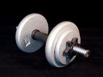 Dumbbell. A weight lifting dumbbell on a black background royalty free stock image