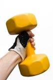 Dumbbell amarelo em uma mão masculina isolada fotografia de stock royalty free