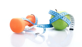 Dumbbell with apple and measure tape Royalty Free Stock Image