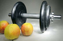 Dumbbell and apples Royalty Free Stock Photos