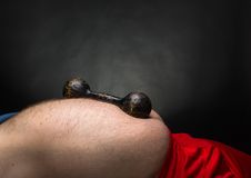 Dumbbell on the belly Stock Images