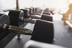 Dumbbell, black rubber in fitness room royalty free stock photo