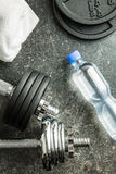 Dumbbell, bottle of water and white towel. Stock Photo