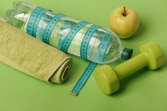 Dumbbell in bright green color, water bottle and measure tape. Dumbbell in bright green color, water bottle, measure tape, towel and fruit on green background royalty free stock images