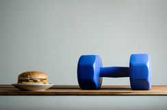 dumbbell and burger on wood table diet, Exercises For Weight Los Royalty Free Stock Photos