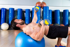 Dumbbell chest press on fit ball man workout. At fitness gym Stock Photo