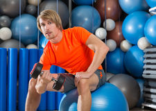 Dumbbell concentrated biceps curl  man fitball. Dumbbell concentrated biceps curl  man workout at gym sit on swiss ball fitball Stock Photo