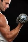 Dumbbell di sollevamento dell'uomo muscolare Fotografia Stock Libera da Diritti