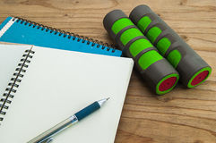 Dumbbell, with diary book on wood background, exercise program Stock Photo