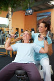 Dumbbell exercises with fitness. Woman doing dumbbell exercises with fitness trainer in gym Royalty Free Stock Image