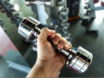 Dumbbell for fitness in hand. A man is engaged in fitness and dors exercise with dumbbells Royalty Free Stock Photography