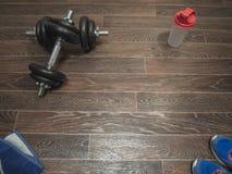 Dumbbell on the floor. Fitness dumbbell on the wooden floor Royalty Free Stock Photo