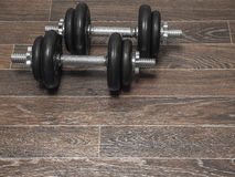 Dumbbell on the floor. Fitness dumbbell on the wooden floor Royalty Free Stock Images