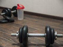 Dumbbell on the floor. Fitness dumbbell on the wooden floor Royalty Free Stock Photography