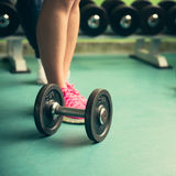 Dumbbell on a flor in fitness gym with legs in background Royalty Free Stock Images