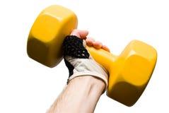 Dumbbell giallo in una mano maschio isolata immagine stock