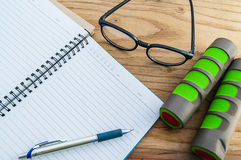 Dumbbell, glasses with diary book on wood background Royalty Free Stock Photo
