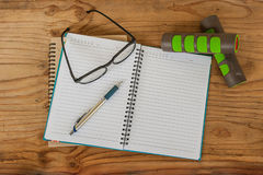 Dumbbell, glasses with diary book on wood background Royalty Free Stock Photography