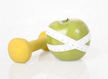 Dumbbell, green apple and measure tape Stock Photo