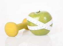 Dumbbell, green apple and measure tape. Dumbbell, fresh green apple and measure tape on a white background stock photo