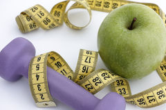 Dumbbell and green apple with tape measure Royalty Free Stock Images