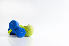 Dumbbell green apple and tape measure. Dumbbell green apple and soft meter. sport and training Stock Photo