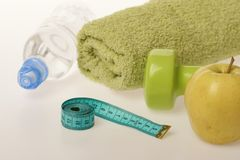 Dumbbell in green color, water bottle, measure tape, towel, fruit. Dumbbell in green color, water bottle, measure tape, towel and fruit on grey background royalty free stock photography