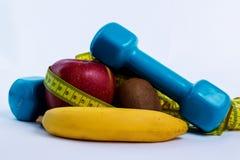 Dumbbell i jabłko, pomarańcze, banan, kiwi bielu tło Zdjęcia Stock