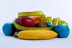 Dumbbell i jabłko, pomarańcze, banan, kiwi bielu tło Fotografia Stock