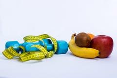 Dumbbell i jabłko, pomarańcze, banan, kiwi bielu tło Zdjęcia Royalty Free