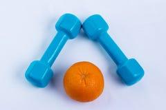 Dumbbell i pomarańczowy biały tło sport Obrazy Stock