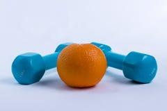 Dumbbell i pomarańczowy biały tło sport Fotografia Stock