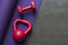 Dumbbell, kettlebell and yoga mat. On black background Royalty Free Stock Photo