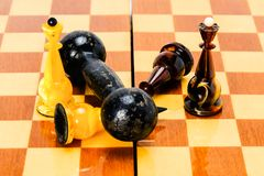 Dumbbell lies on a chessboard, on white chess king, black have fallen nearby, with Queens. The victory of power over the stock photos