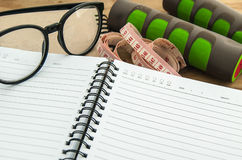 Dumbbell,measuring tape, glasses with diary book Royalty Free Stock Photos
