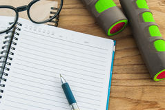 Dumbbell,measuring tape, glasses with diary book Royalty Free Stock Photography