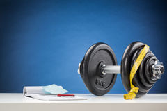 Dumbbell with Measuring Tape and Notebook Royalty Free Stock Images