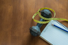 Dumbbell, Measuring Tape, Pencil and notebook indicating workout. Plan on wooden table Royalty Free Stock Photos