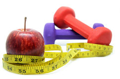 Dumbbell with measuring tape and red apple. Health concept Stock Image