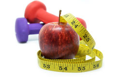 Dumbbell with measuring tape and red apple. Health concept Stock Photography