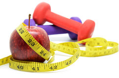 Dumbbell with measuring tape and red apple. Health concept Royalty Free Stock Photo