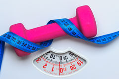 Dumbbell measuring tape on weight scale. Fitness Royalty Free Stock Photo