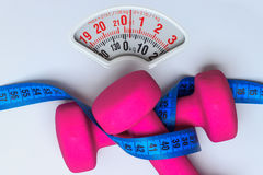 Dumbbell measuring tape on weight scale. Fitness Stock Photography