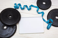 Dumbbell and measuring tape on white boards Royalty Free Stock Image