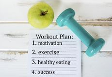 Dumbbell,Notebook with Workout Plan  and Green Apple. Green dumbbell, notebook and green apple .Motivation,Exercise,Healthy Eating,Success Stock Image