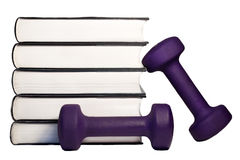 A dumbbell and stack of books for the concept of learning to be fit and healthy. Stock Images