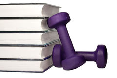 A dumbbell and stack of books for the concept of learning to be fit and healthy. Stock Photography