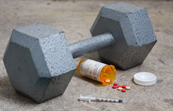 Dumbbell with Steroids and Needle. On concrete royalty free stock image