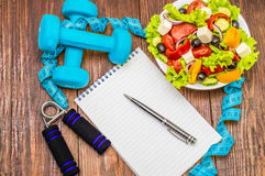 Dumbbell, vegetable salad and measuring tape on rustic wooden table. royalty free stock photography